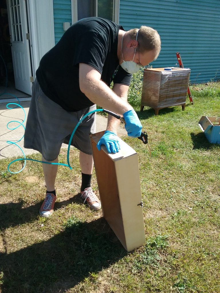 As we cleaned the dresser, we wore gloves and masks due to the mouse droppings. Here Erik is using compressed air to blow the detritus out of a drawer. September 2018.
